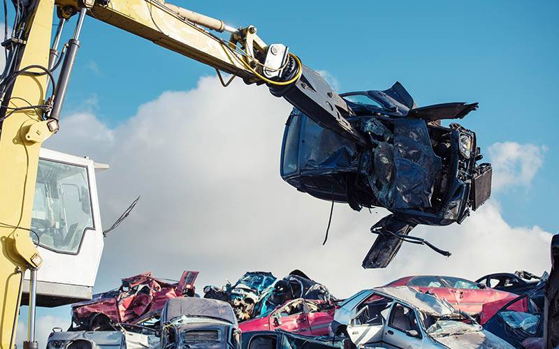 Crane lifting car onto scrap heap