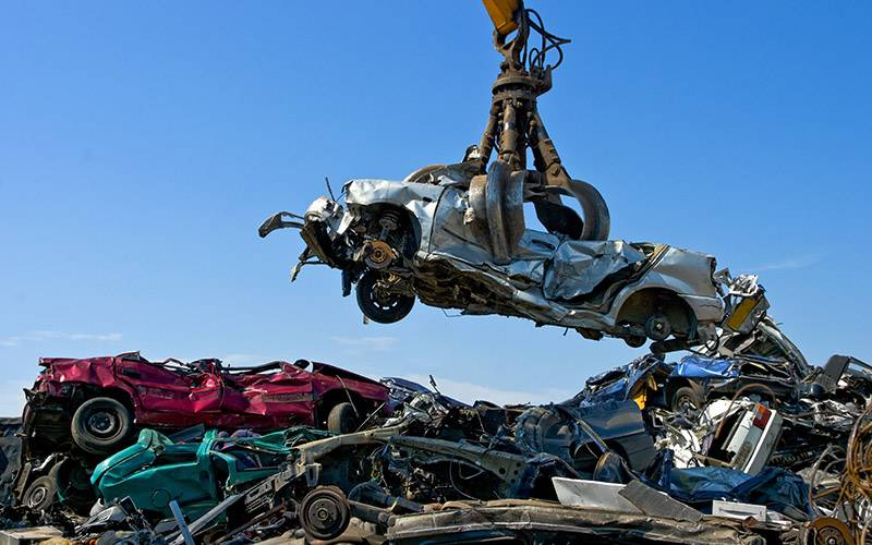 crane lifting car above scrap heap